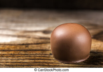 Close up of one round candy over wood with copy space