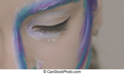 Close up of open bright green eye of the girl with art make up