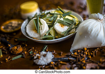 Close up of organic salad of White radish with spring onions, olive oil, black pepper, salt and clove powder with some sour cream and curd on wooden surface in a glass plate used as medicine for lever.