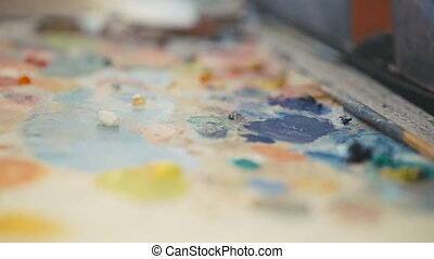 Close up of paintbrush mixes paint on the palette in 4K