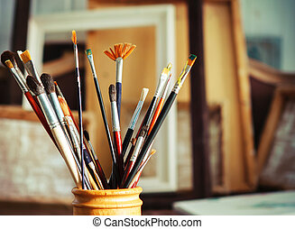 Close up of painting brushes in studio of artist. Tones...