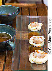 Close up of pan seared sea scallops and a cup of cider