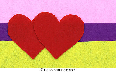 Close up of paper heart shapes on yellow, purple and pink background