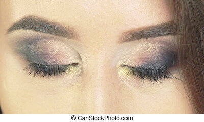 Close-up of passion playful woman eyes opening, make up. Slow motion