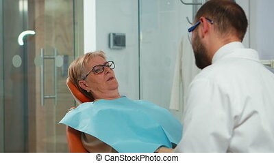 Close up of patient wearing dental bib talking with dentist before intervetion. Orthodontist speaking to woman with toothache sitting on stomatological chair while nurse preparing sterilized tools.