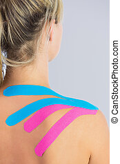 Close up of patients shoulder with applied pink and blue...