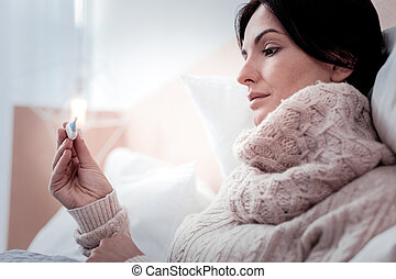 Close up of peaceful woman holding thermometer in hands