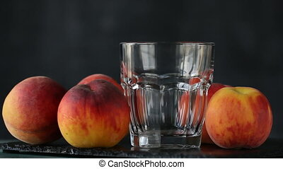 Close-up of peach juice poured into a glass, black background