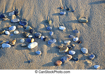 Close-up of pebbles in the sunlight on sandy beach