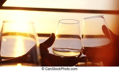 Close up of people holding glasses of white wine, making a...