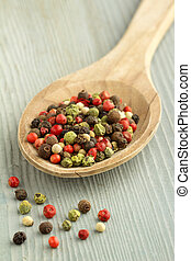 peppercorn mix in a wooden spoon - close up of peppercorn...
