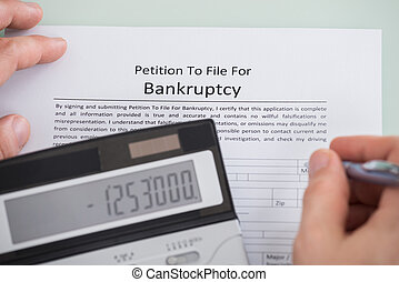 Person Hand And Calculator Over Bankruptcy Form
