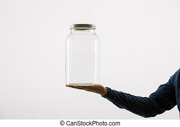 Close up of person hand holding an empty glass jar isolated over white background with copy space.