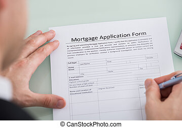 Person Hand Over Mortgage Application Form