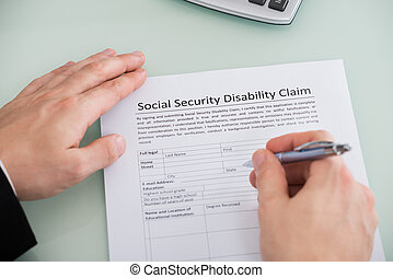 Person Hand Over Social Security Disability Claim Form -...