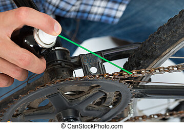Close-up Of Person Hands Lubricating Bike Chain