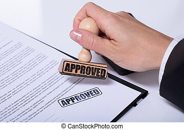 Person Hands Using Stamper On Document With The Text Approved
