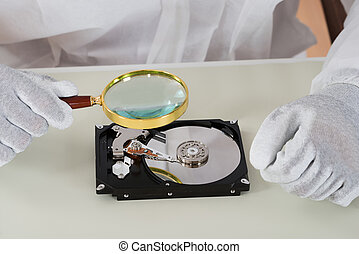 Person Holding Magnifying Glass Over Harddisk