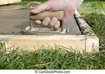 Close up of person using concrete edging tool