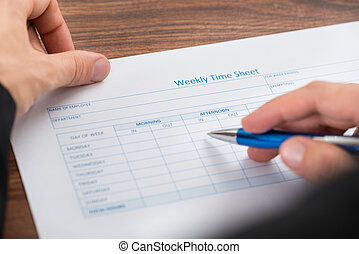 businesswoman filling weekly time sheet high angle view of