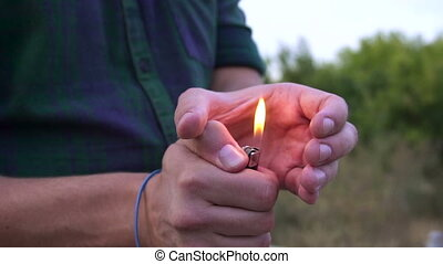 close up of person's hand light the fire on lighter. the bright lighter flame in slow motion
