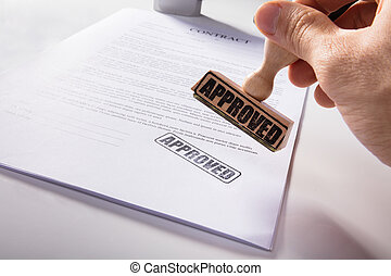 Person's Hand Stamping Approved On Contract Paper