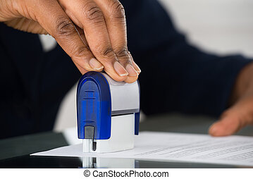 Person's Hand Stamping Document - Close-up Of Person's Hand...