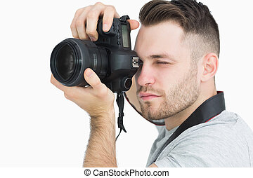 Close-up of photographer with photographic camera over white...