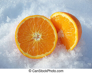 cut orange - Close-up of pieces of cut orange in white snow...