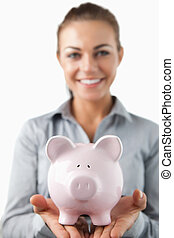 Close up of piggy bank being held by smiling female bank assistant against a white background