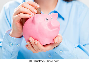 Close-up of piggy bank pig and coins in female hands