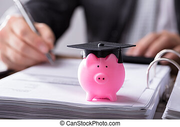 Close-up Of Piggybank With Graduation Cap