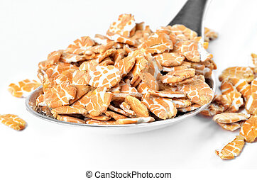 Close-up of pile of oat flakes on a spoon isolated on a white background