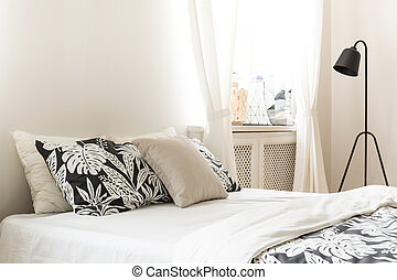 Close-up of pillows and leaf motif cover on a bed in a bright bedroom interior. Black metal lamp next to the bed. Real photo.