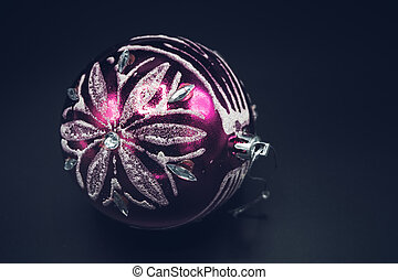 Close-up of pink and silver christmas ball on black background.