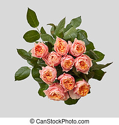 close-up of pink bouquet of rose with green leaves on a gray...