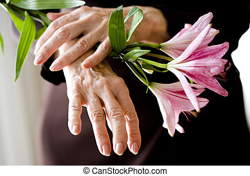 Close-up of pink flowers held by elderly woman