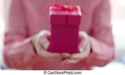 Close up of pink gift box with red ribbon in womans hands
