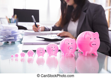 Close-up Of Pink Piggybank In A Row