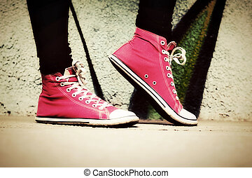 Close up of pink sneakers worn by a teenager. Grunge graffiti wall, retro vintage style