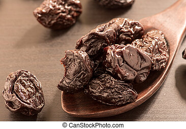 Close up of pitted prunes on black color wooden spoon