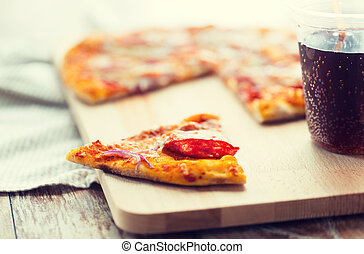 close up of pizza with carbonated drink on table - fast...