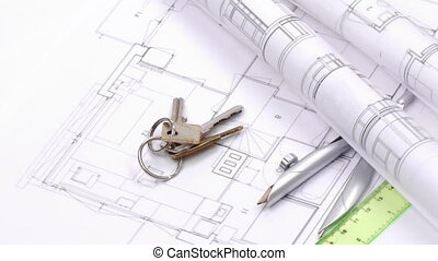 Close-up of plans, compass and keys turning