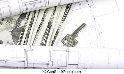 Close-up of plans, dollars and keys turning