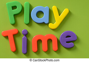 Close up of Play Time words in colorful plastic letters on green background