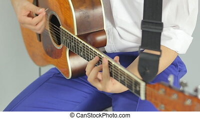 Close-up of playing on a wooden guitar in the studio on a white background