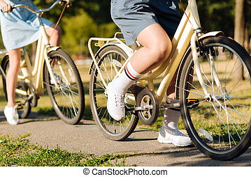 Close up of pleasant friends riding bicycles
