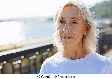 Close up of pleasant senior woman standing on the bridge