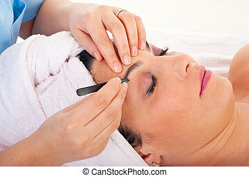 Close up of beautician hands plucking woman eyebrows in a spa retreat