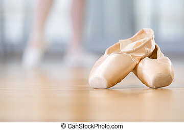 Close up of pointes for ballet lying on the wooden floor in...
